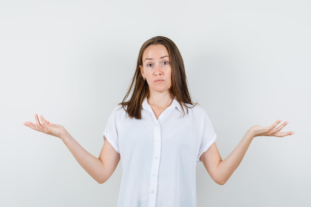 Young lady showing what to do gesture in white blouse and looking sorrowful