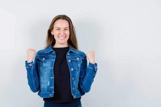 Giovane donna che mostra il gesto del vincitore in camicetta, giacca e guardando beato, vista frontale.