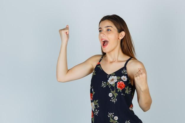 Giovane donna che mostra il gesto del vincitore in camicetta e sembra felice, vista frontale.