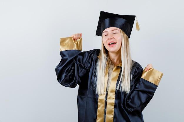 アカデミックドレスで勝者のジェスチャーを示し、至福に見える若い女性。