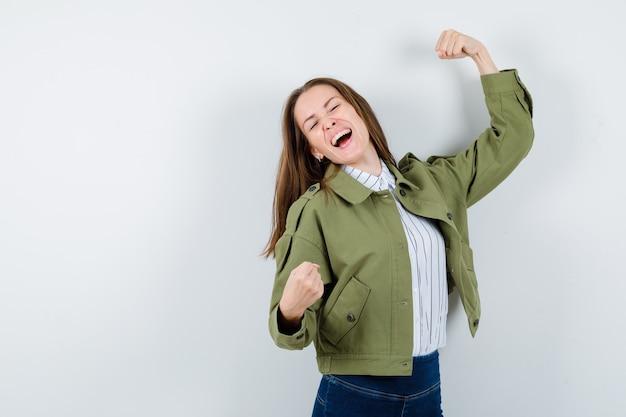 ブラウス、ジャケットで勝者のジェスチャーを示し、至福に見える若い女性。