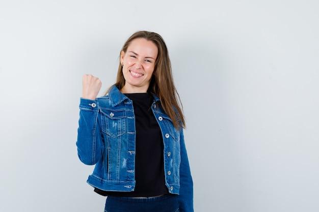 ブラウス、ジャケット、自信を持って、正面図で勝者のジェスチャーを示す若い女性。