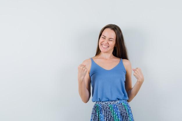 파란색 블라우스, 치마 및 유쾌한 찾고 승자 제스처를 보여주는 젊은 아가씨. 전면보기. 텍스트를위한 공간