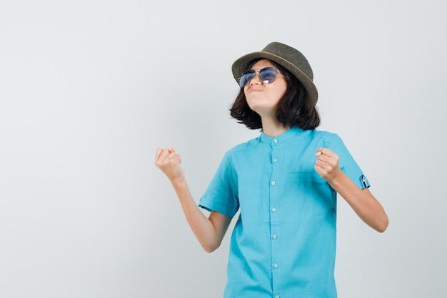 青いシャツ、帽子、サングラスで勝者のジェスチャーを示し、幸せそうに見える若い女性。