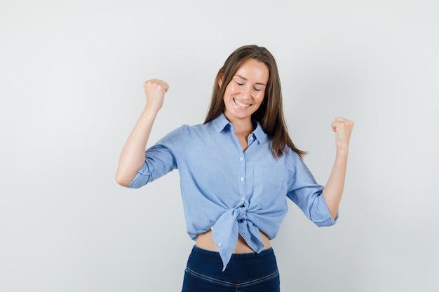 青いシャツ、ズボンで勝者のジェスチャーを示し、幸せそうに見える若い女性。