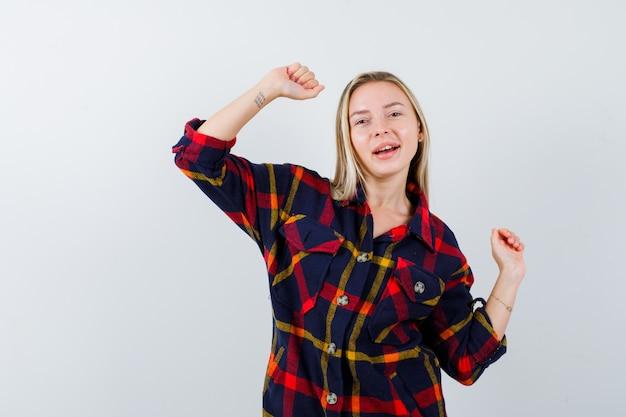 Молодая леди показывает жест победителя в клетчатой рубашке и выглядит блаженно. передний план.