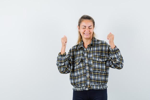체크 셔츠에 우승자 제스처를 보여주는 젊은 아가씨 행복을 찾고. 전면보기.