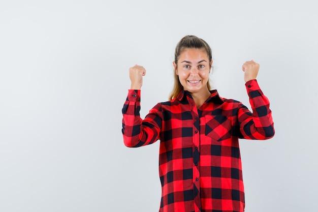 체크 셔츠에 우승자 제스처를 보여주는 젊은 아가씨 행복 찾고