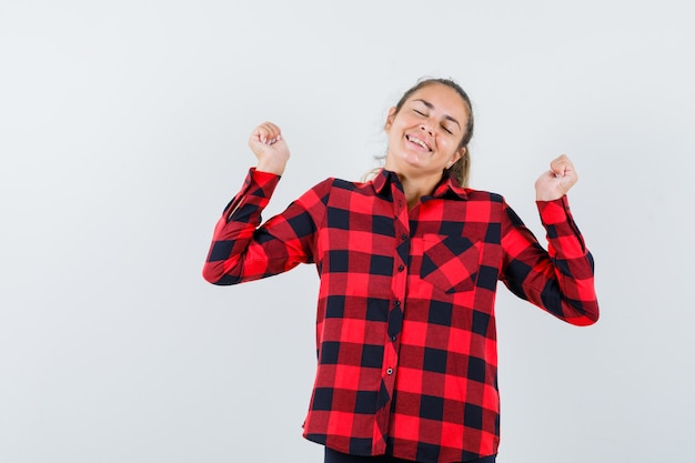 チェックシャツで勝者のジェスチャーを示し、幸せそうに見える若い女性