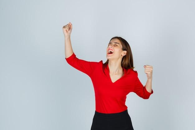 Молодая дама показывает жест победителя в красной блузке, черной юбке и выглядит удачливой