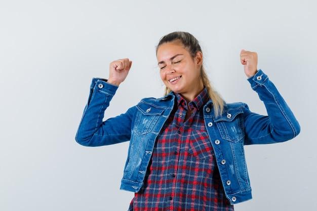 젊은 아가씨 셔츠, 재킷에 우승자 제스처를 보여주는 행복, 전면보기.