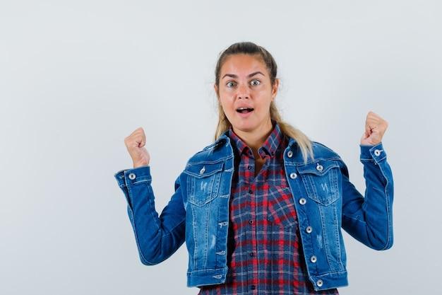 셔츠, 재킷에 승자 제스처를 보여주는 젊은 아가씨 운이 좋은 찾고. 전면보기.