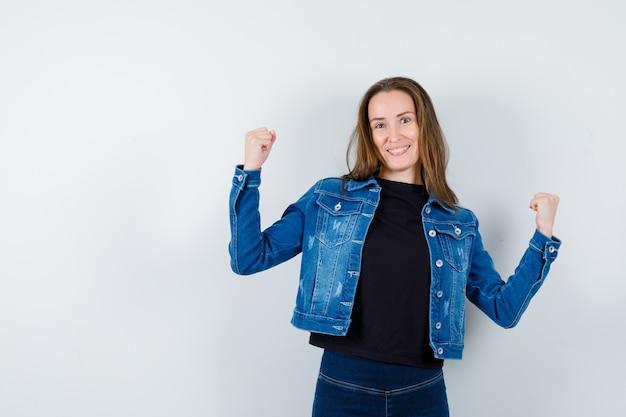 シャツ、ジャケットで勝者のジェスチャーを示し、幸運に見える若い女性。正面図。