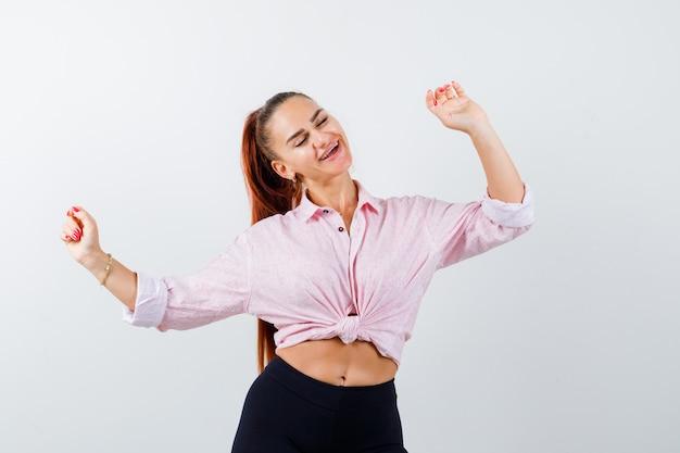 Юная леди показывает жест победителя в рубашке, штанах и выглядит счастливой. передний план.