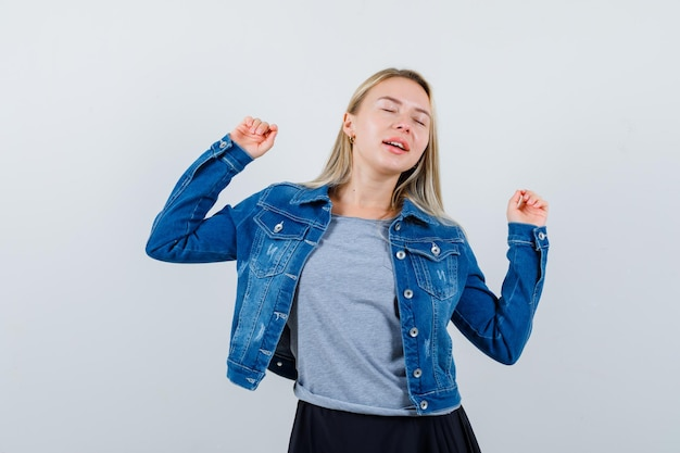 T- 셔츠, 데님 재킷, 스커트에 승자 제스처를 보여주고 운이 좋은 젊은 아가씨