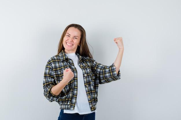 T- 셔츠, 재킷, 청바지에 승자 제스처를 보여주는 행복, 전면보기 젊은 아가씨.