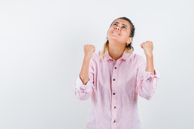 Giovane signora che mostra il gesto del vincitore in camicia rosa e che sembra grata