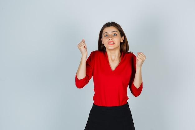 Giovane donna che mostra il gesto del vincitore in camicetta rossa, gonna e aspetto beato
