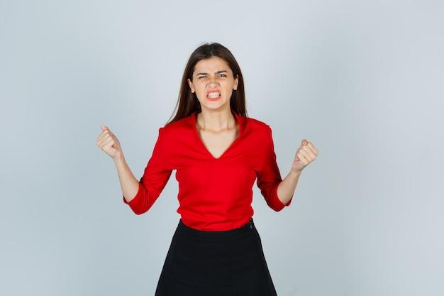 Giovane signora che mostra il gesto del vincitore in camicetta rossa, gonna e sembra fortunata