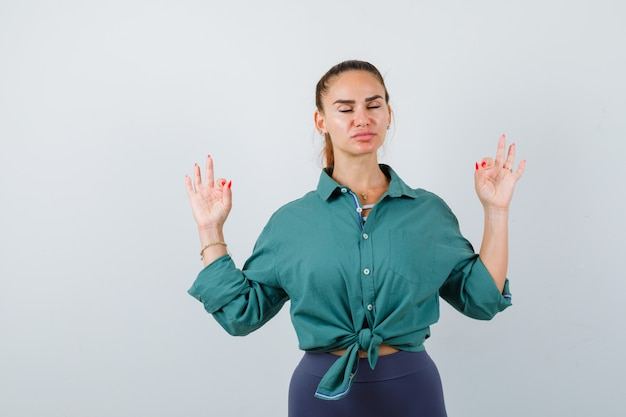 Young lady showing yoga gesture with shut eyes in green shirt and looking relaxed. front view.