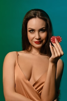 Young lady in silk beige dress she smiling showing two red chips posing against green studio wall