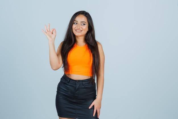 Giovane donna in canottiera, minigonna che mostra il gesto giusto e sembra felice, vista frontale.