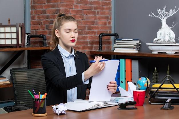 Молодая дама сидит за столом и читает свои заметки в записной книжке в офисе