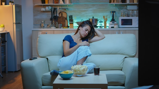 Young lady sleeping on couch watching tv. tired exhausted lonely sleepy woman in pajamas falling asleep on sofa in front television, closing eyes while watching movie at night in living room