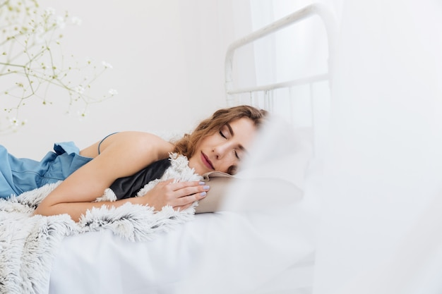 Young lady sleeping indoors in bed. eyes closed.