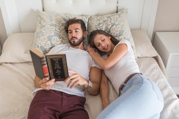 Young lady sleeping near reading boyfriend
