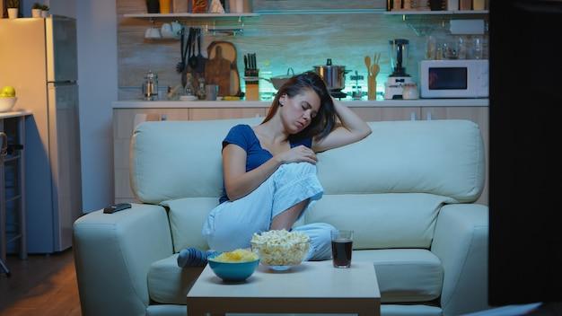 テレビを見ながらソファで寝ている若い女性。夜、居間で映画を見ながら目を閉じて、テレビの前のソファで眠りに落ちるパジャマ姿の疲れた孤独な眠そうな女性