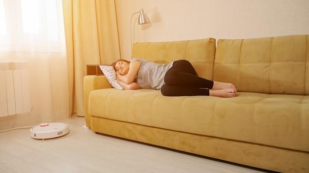 白い丸い現代的なロボット掃除機がリビングルームの木製の床をフーバーしながら、若い女性は枕と快適なソファで寝る