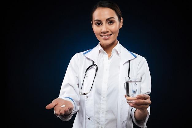 若い女性の笑みを浮かべて、分離された錠剤と水のガラスを保持