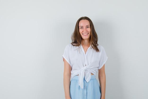 Девушка улыбается в блузке, юбке и выглядит весело