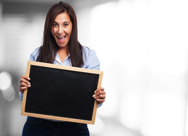Young lady smiling while holding a slate board
