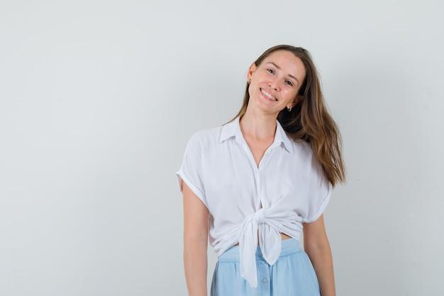 ブラウス、スカート、前向きに見ながら笑顔の若い女性