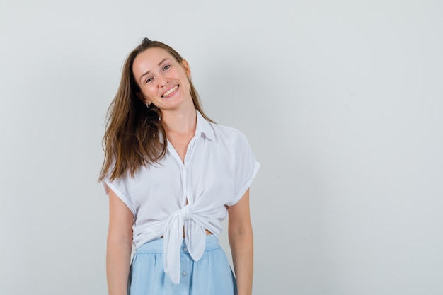 Young lady smiling while looking at front in blouse, skirt and looking positive
