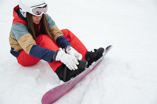 Сноубордистка юная леди лежит на склонах морозным зимним днем