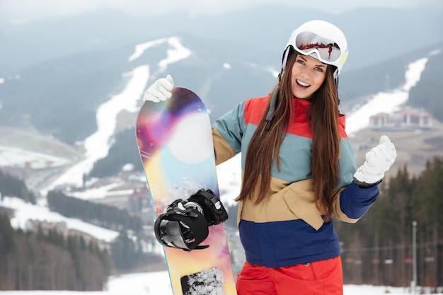 Сноубордистка молодой леди на склонах морозным зимним днем держит сноуборд в руках