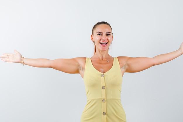 Giovane donna che allarga le braccia lateralmente in abito giallo e sembra felice, vista frontale.