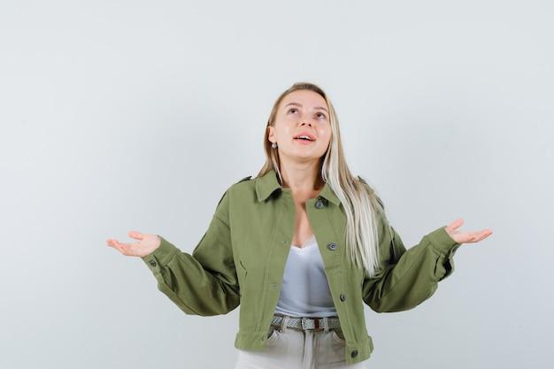 手を広げて、ジャケット、ズボンで見上げて、幸せそうに見える若い女性、正面図。