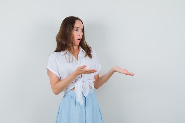 白いブラウス、青いスカートで何かを見せて、唖然と見えるために彼女の開いた手のひらを脇に広げている若い女性