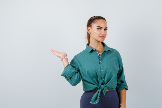 Giovane signora che allarga il palmo da parte in camicia verde e sembra sicura. vista frontale.