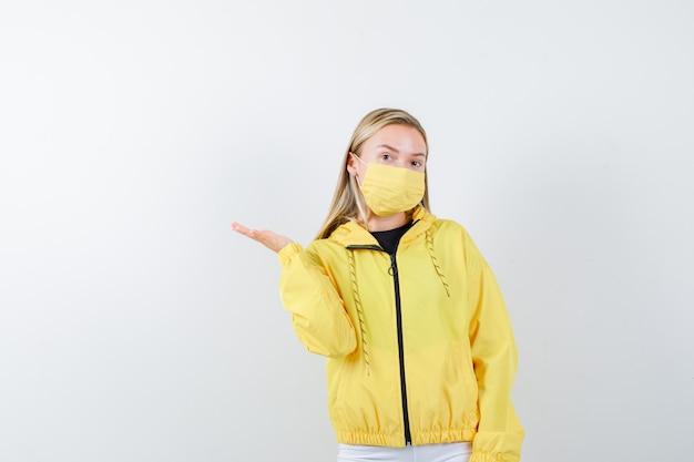 ジャケット、ズボン、マスクで脇に手のひらを広げ、自信を持って、正面図を探している若い女性。