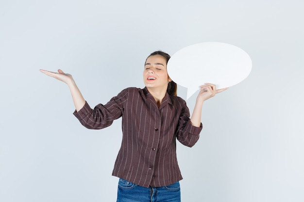 手のひらを広げて、シャツ、ジーンズで紙のポスターを保持し、幸せそうに見える、正面図。