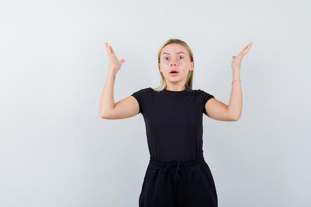Девушка в футболке, штанах разводит ладони в стороны и выглядит встревоженной. передний план.