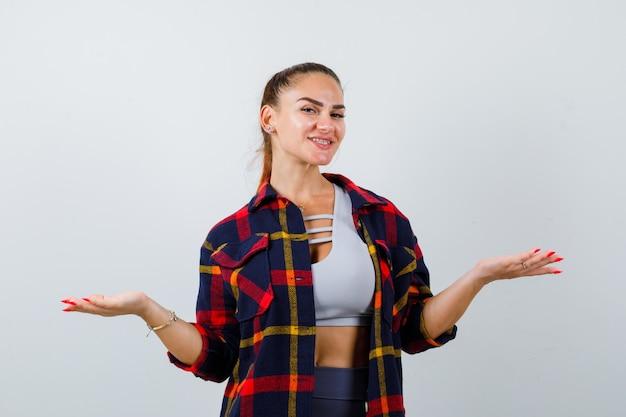 젊은 아가씨는 손바닥을 옆으로 펼치고 격자 무늬 셔츠를 입고 쾌활한 모습을 보입니다. 전면보기.
