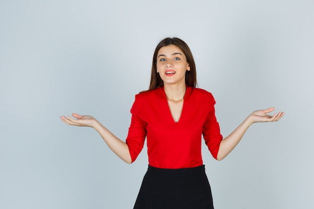 Giovane donna che allarga le palme da parte in camicetta rossa, gonna e sembra allegra