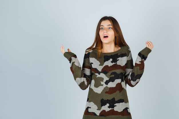 Giovane donna che allarga le palme da parte in maglione e sembra perplessa