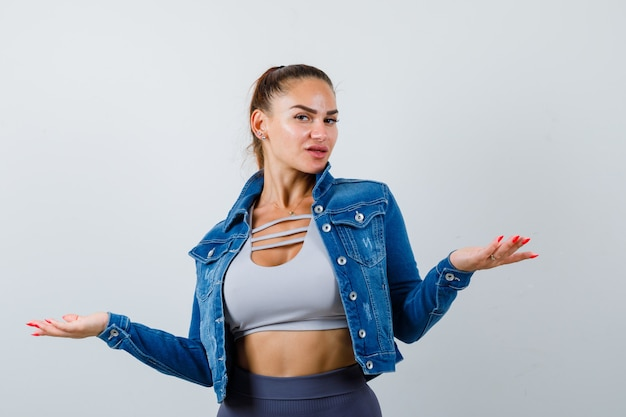 Giovane donna che allarga le palme da parte in alto, giacca di jeans e sembra sicura, vista frontale.